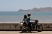 A father and daughter stop their motorbike to look out into Dili Harbour.